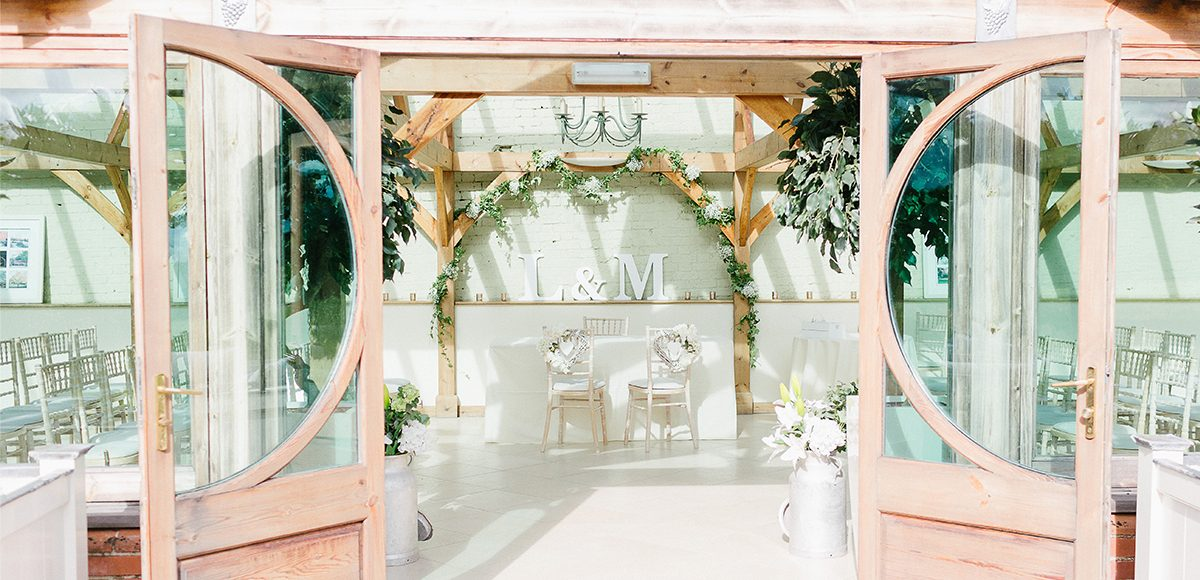 Decorate the Orangery with wooden letters and milk churns for a rustic wedding style