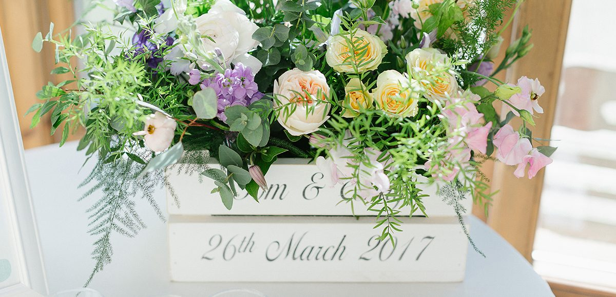 A crate filled with wedding flowers creates stunning spring wedding decorations in the Orangery