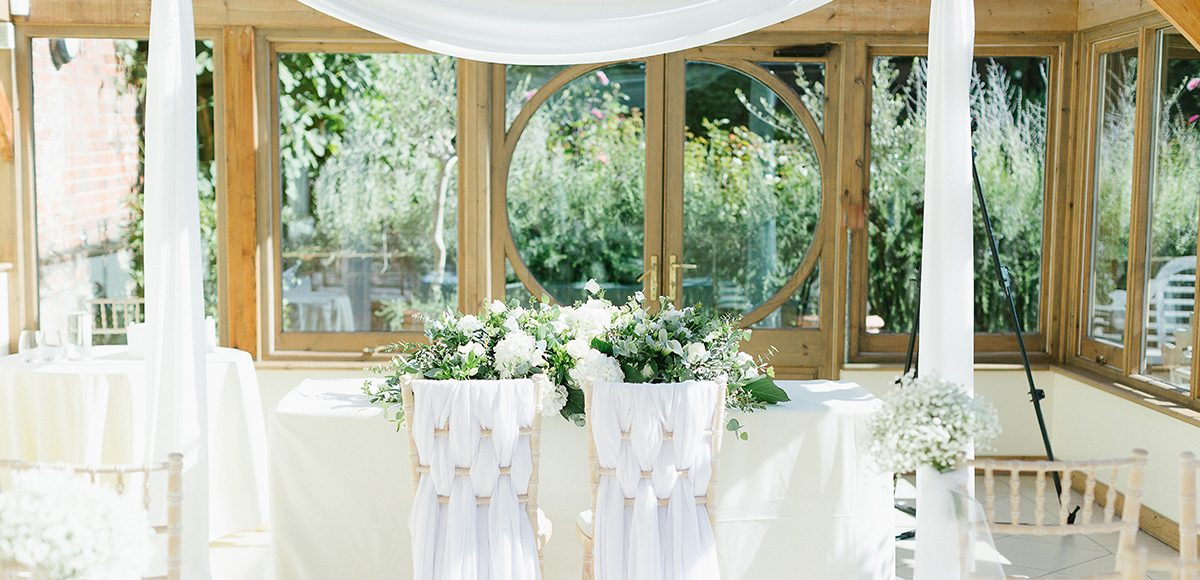 White flowers and drapes decorate the Orangery at Gaynes Park for a white wedding