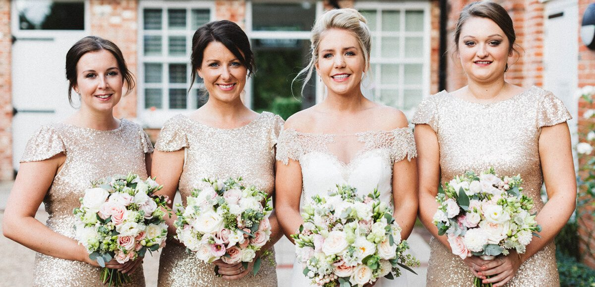 The bride stands with her bridesmaids before her wedding ceremony at Gaynes Park in Essex
