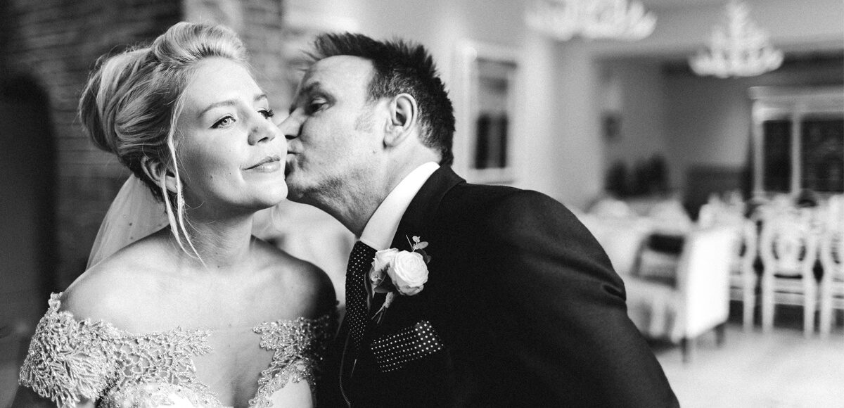 The father of the bride gives her an emotional kiss before the wedding ceremony