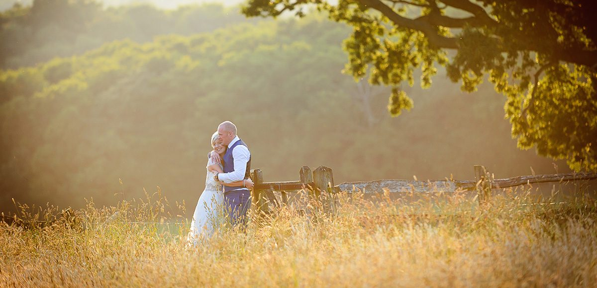 A bride and groom enjoy the countryside surrounding Gaynes Park wedding venue in Essex