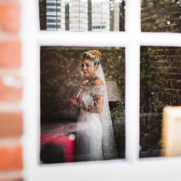 A sneak peak of the bride through a window before her wedding ceremony at Gaynes Park