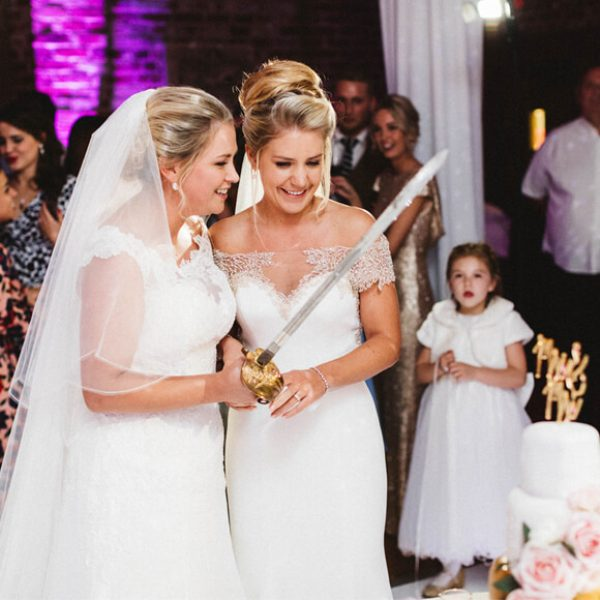 Brides cut the cake during their evening wedding reception in the Mill Barn at Gaynes Park
