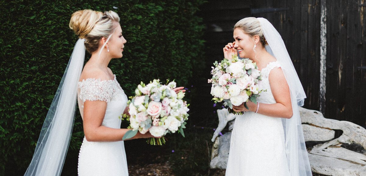 The brides share a first look moment before their wedding ceremony in the Orangery at Gaynes Park
