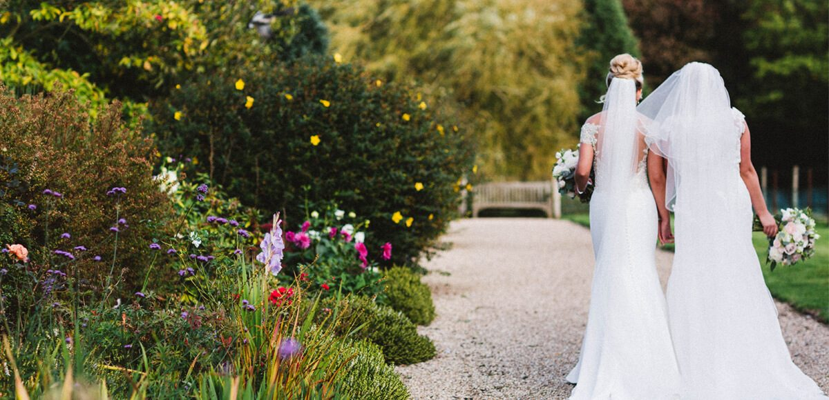 The brides take a stroll down the Long Walk at Gaynes Park wedding venue in Essex