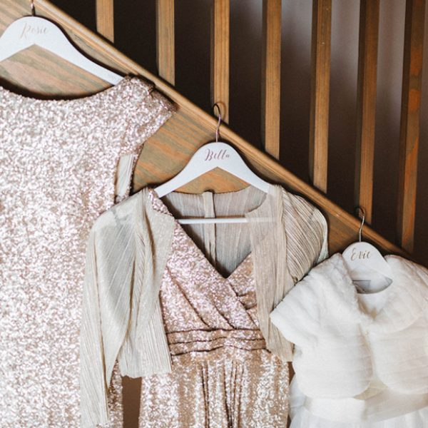 Gold bridesmaid dresses and a cream flower girl dress hang from the staircase in the Apple Loft barn at Gaynes Park