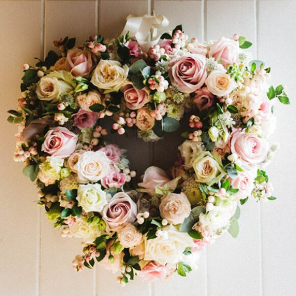 A heart shaped floral wreath hangs on the door of the Apple Loft Cottage at Gaynes Park in Essex
