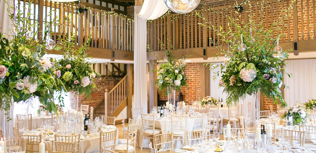 The Mill Barn at Gaynes Park wedding venue in Essex is set up for a beautiful wedding reception
