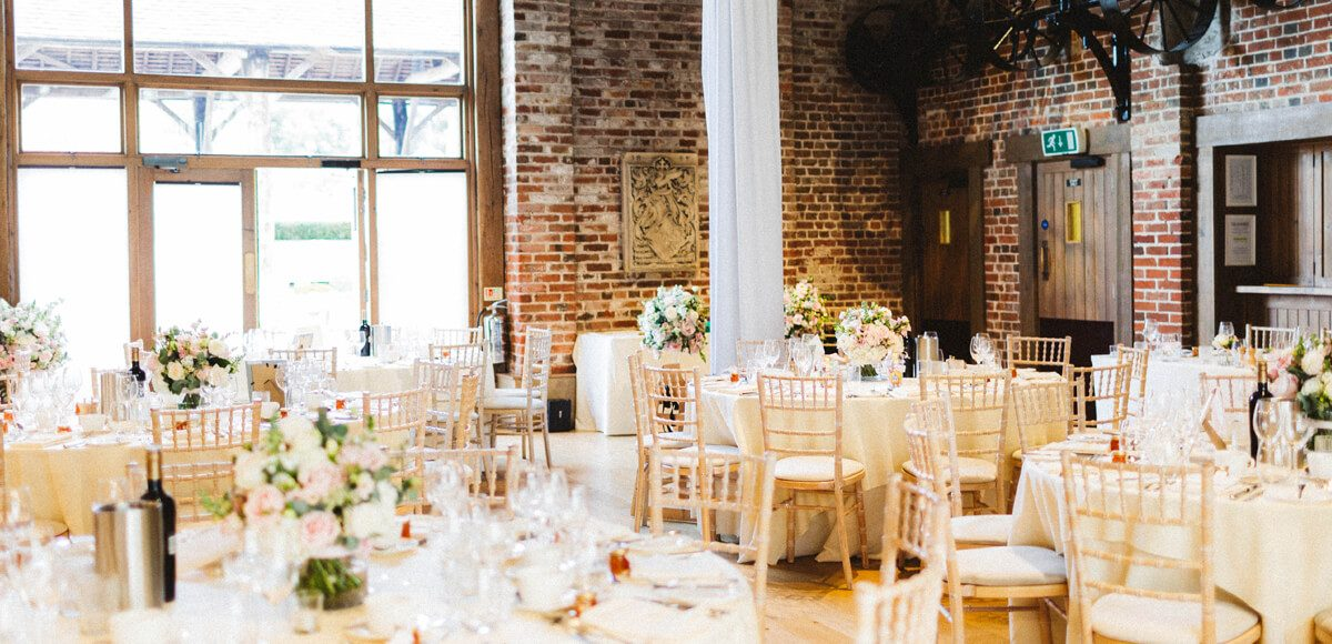 The Mill Barn at Gaynes Park in Essex is set up for an elegant wedding reception