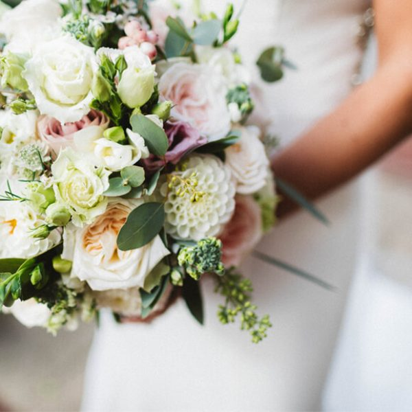 A pink and white bridal bouquet is held by one of the brides before her wedding ceremony at Gaynes Park
