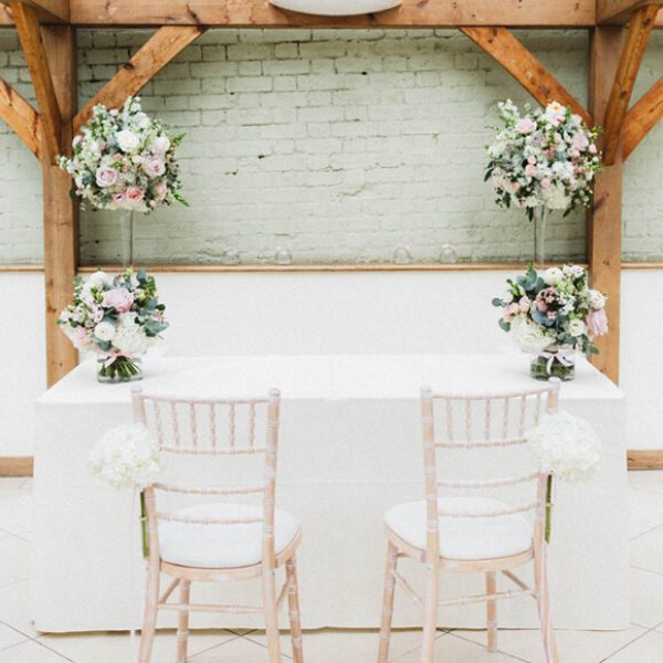 The registrars table for the wedding ceremony is decorated with pink and white wedding flowers