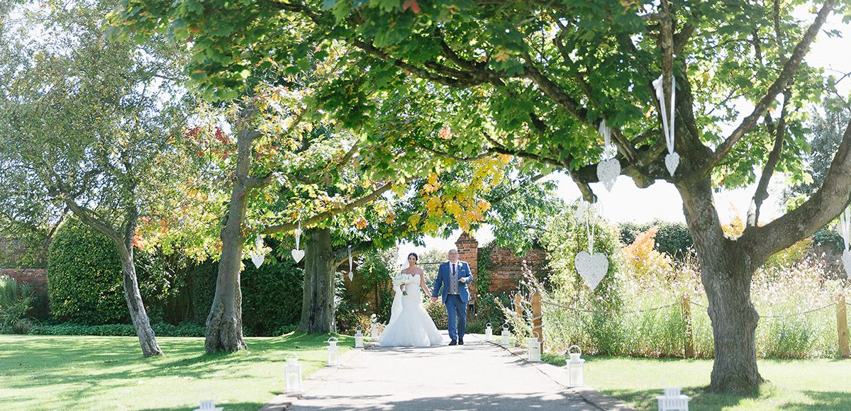 The bride and her father walk down the wedding aisle towards the wedding ceremony at Gaynes Park
