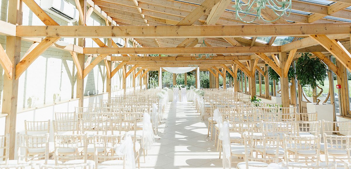 At Gaynes Park wedding venue in Essex the Orangery is set up for an elegant wedding ceremony