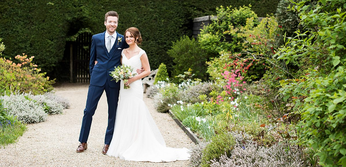 A bride and groom enjoy the blooms on Long Walk at Gaynes Park wedding venue in Essex