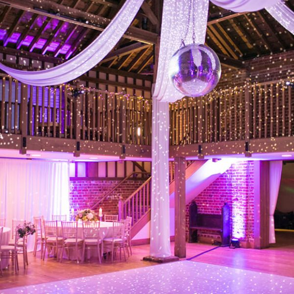 Coloured lights and a glitterball add glamour to this rustic barn wedding venue