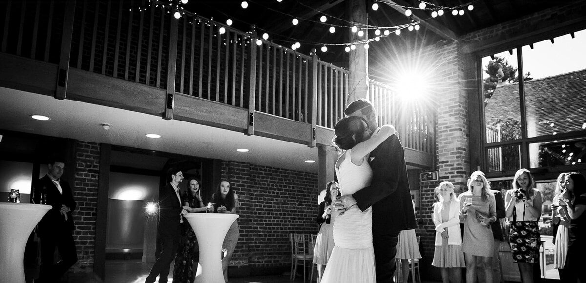 A bride and groom enjoy their first dance in the Mill Barn beneath strings of fairylights