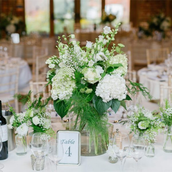 A beautiful white and green floral table centrepiece in the Mill Barn at Gaynes Park wedding venue in Essex