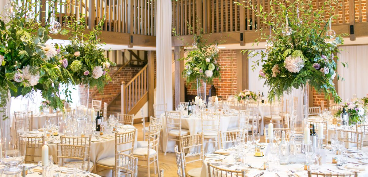 Tall floral vases were used to decorate the Mill Barn for an elegant wedding breakfast at Gaynes Park