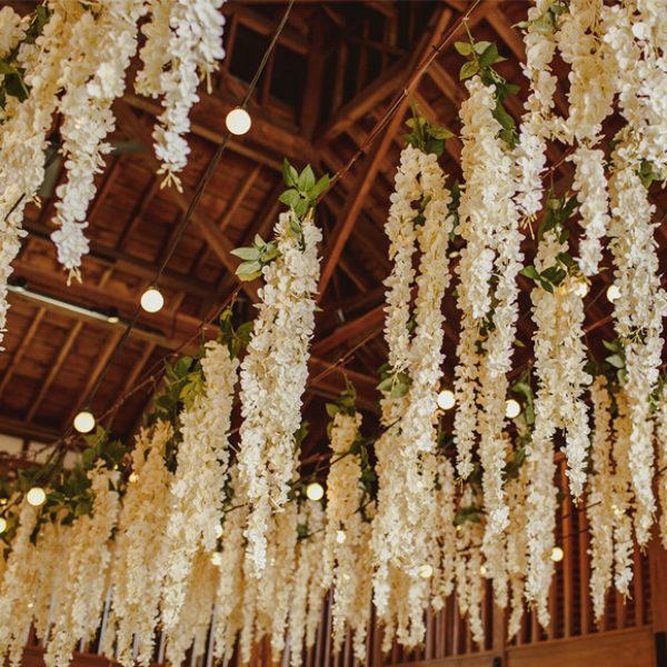 Stunning florals hang above a wedding reception in the Mill Barn at Gaynes Park in Essex