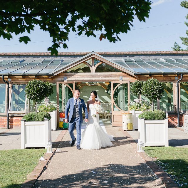 : A Bride and groom take a moment away from guests I the gardens at Gaynes Park in Essex