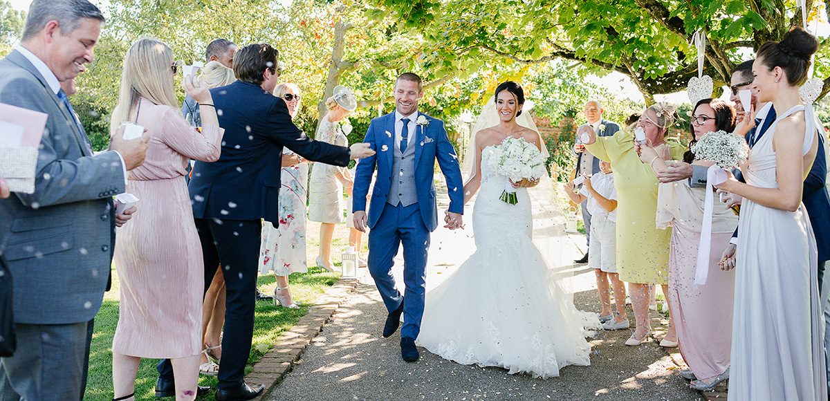 Wedding guests throw confetti over the newlyweds after their wedding ceremony at Gaynes Park