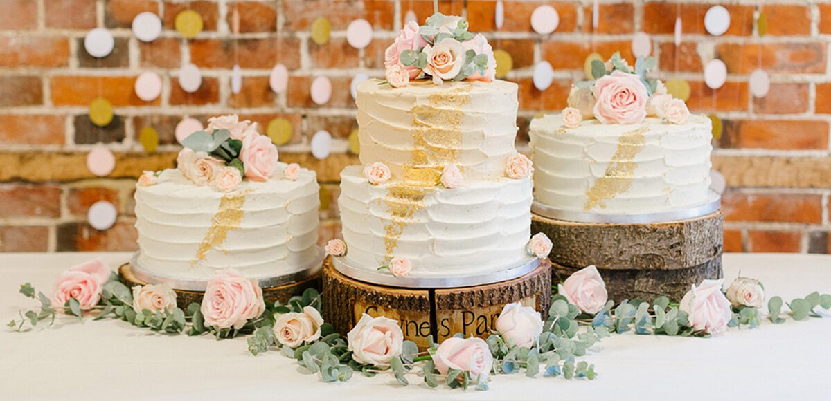 Three rustic wedding cakes wait to be cut during an evening wedding reception at Gaynes Park