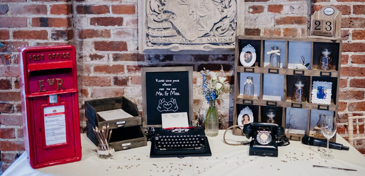A vintage wedding gift table at Gaynes Park is decorated with a red post-box