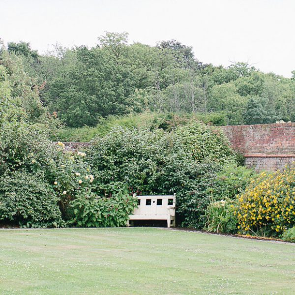 A pretty bench sits within the stunning Walled Gardens at Gaynes Park wedding venue in Essex