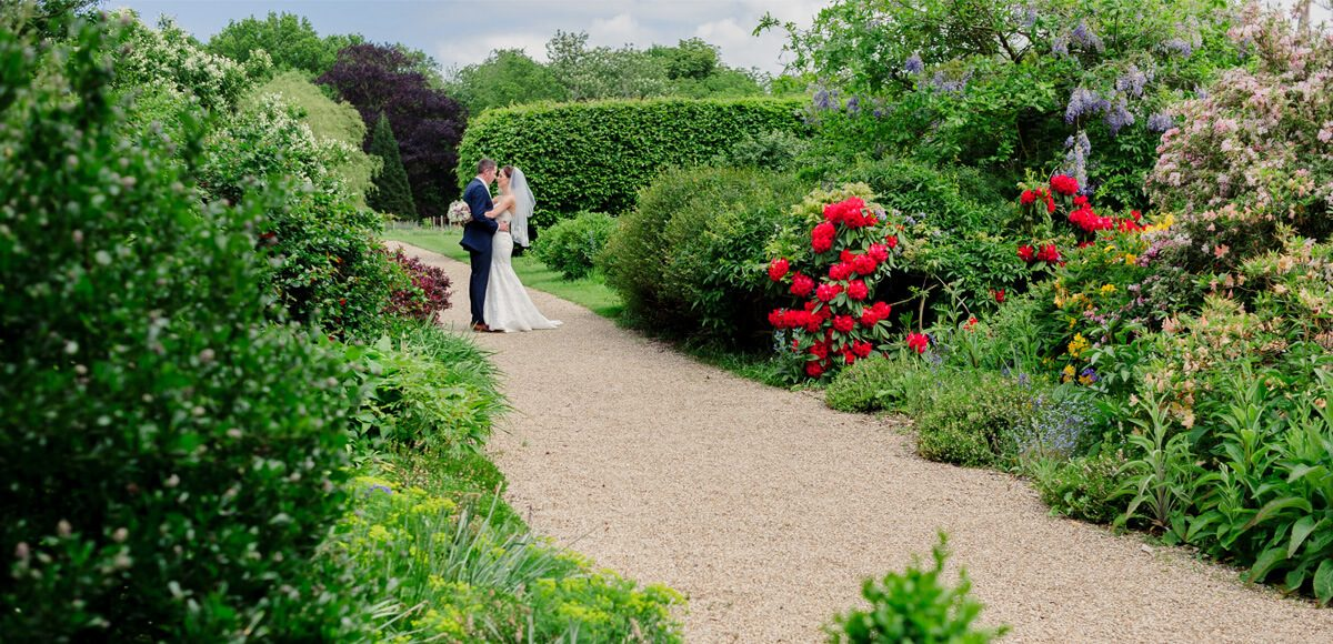 A bride and groom share a moment on the stunning Long Walk at Gaynes Park wedding venue in Essex