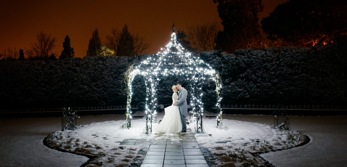 The bride and groom stand under the beautifully lit Pavillion at Gaynes Park in Essex on their wedding evening