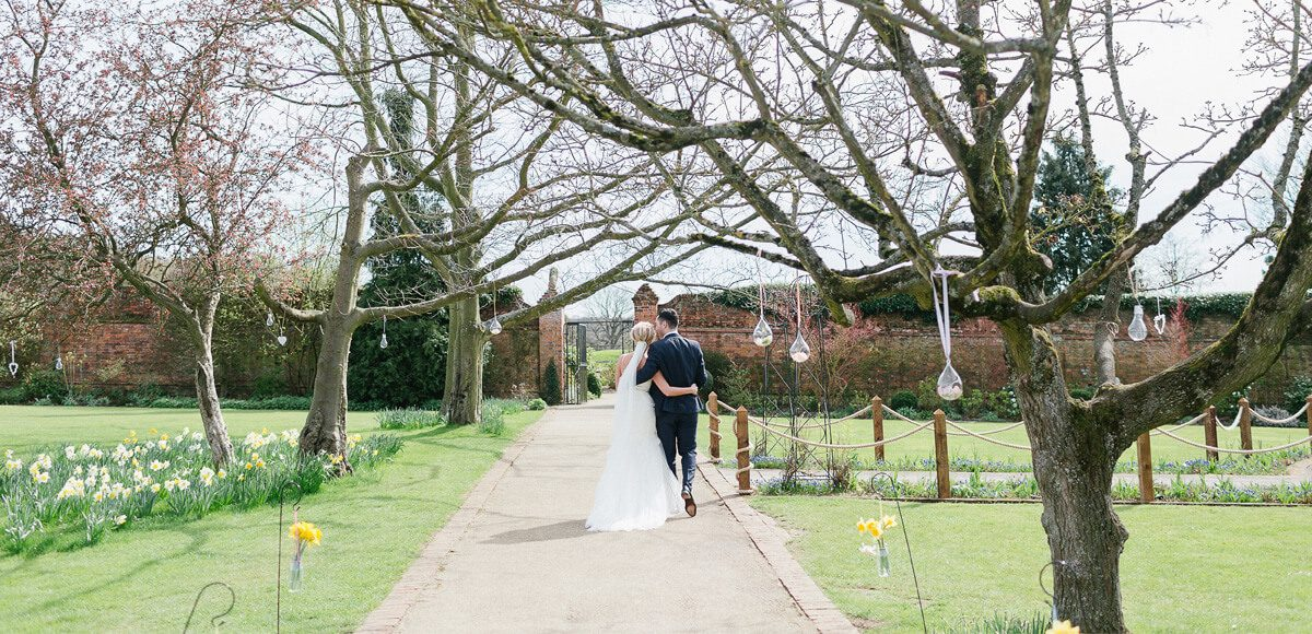 Wedding decorations hang from the trees in the Walled Gardens at Gaynes Park as the bride and groom take a stroll