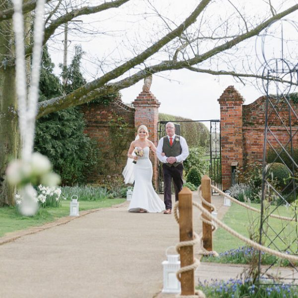 During a beautiful spring wedding the bride and her father walk down the wedding aisle in the Walled Gardens at Gaynes Park