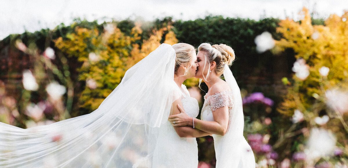 Brides share a kiss in the beautiful gardens at Gaynes Park wedding venue in Essex
