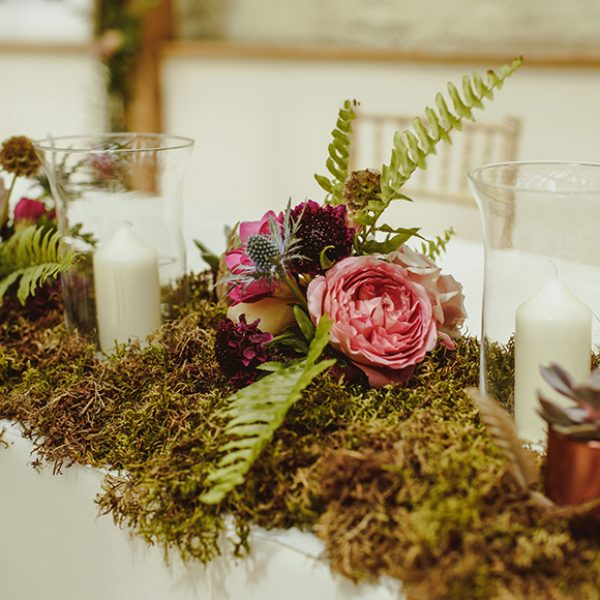 Hurricane vases are filled with candles to add romantic lighting to this summer wedding ceremony at Gaynes Park