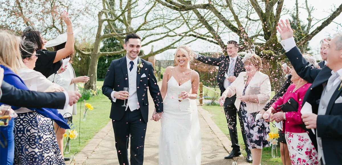 In the Walled Gardens at Gaynes Park wedding guests surround the newlyweds for a fun wedding confetti moment