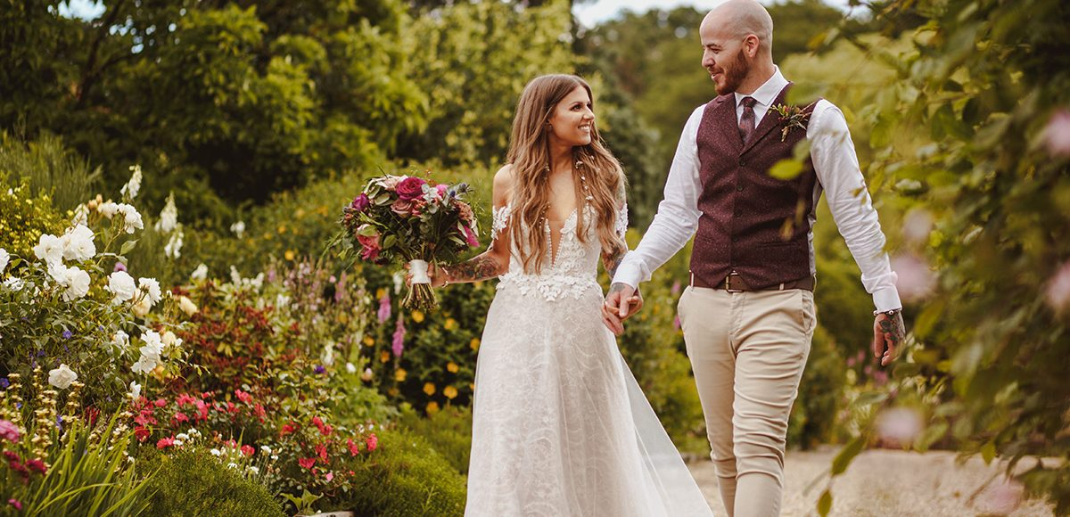 The newlyweds explore the stunning gardens at Gaynes Park wedding venue in Essex