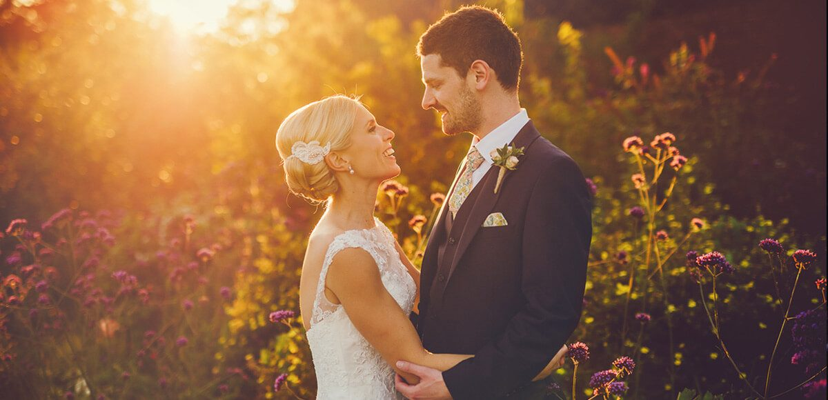 Newlyweds enjoy a moment in the gardens during the sunset on their wedding day at Gaynes Park in Essex