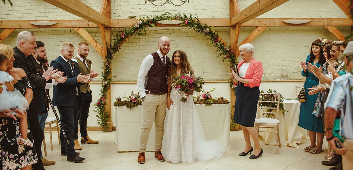 The newlyweds celebrate after getting married at Gaynes Park wedding venue in Essex