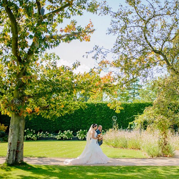 A bride and her father make their way down the beautiful wedding aisle in the Walled Gardens at Gaynes Park