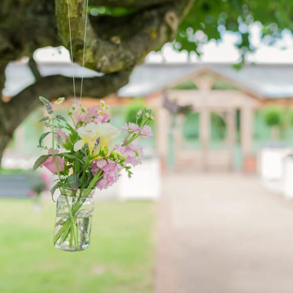 Wedding flowers sit in glass jars that hang from the trees in the Walled Garden at Gaynes Park – wedding ideas