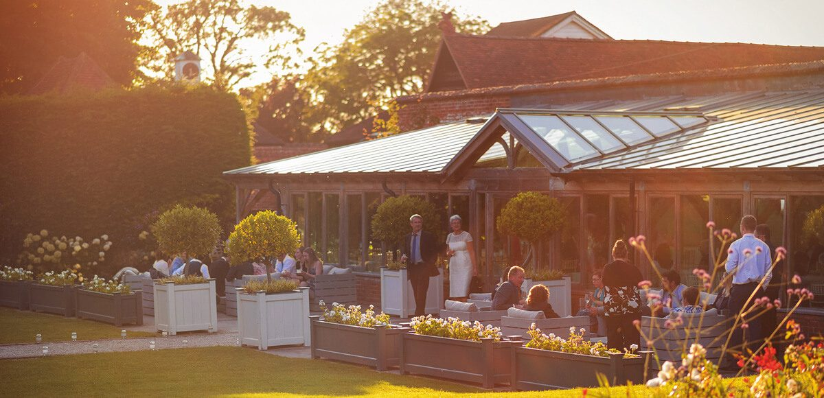 Wedding guests look out in to the Walled Gardens at Gaynes Park as they relax in a seating area outside the Orangery