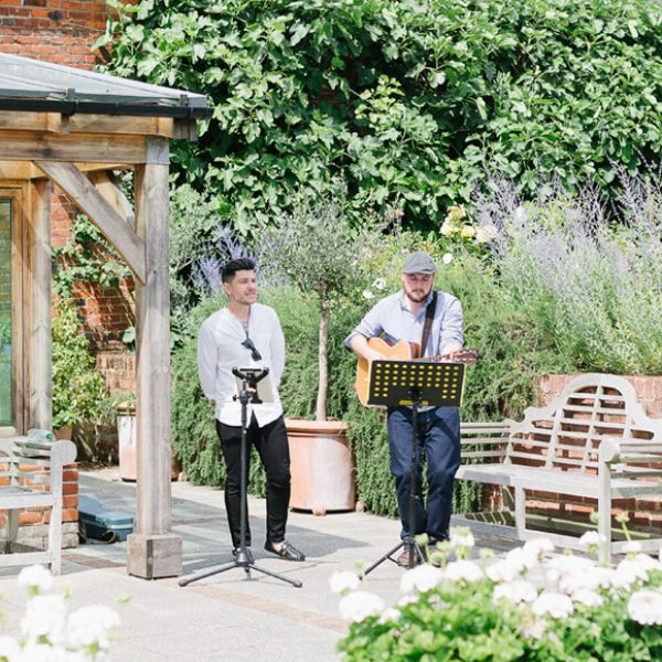 A musical duo play wedding music in the Walled Gardens during a drinks reception at Gaynes Park