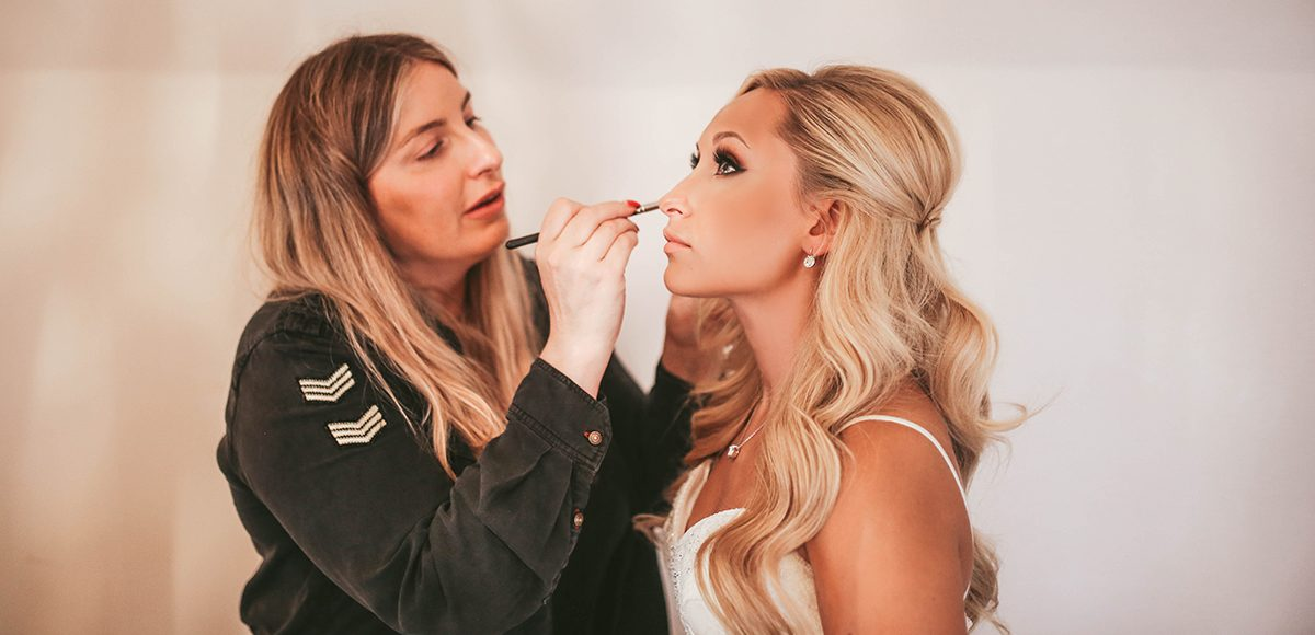 Bridal makeup is applied to the bride before her wedding ceremony at Gaynes Park