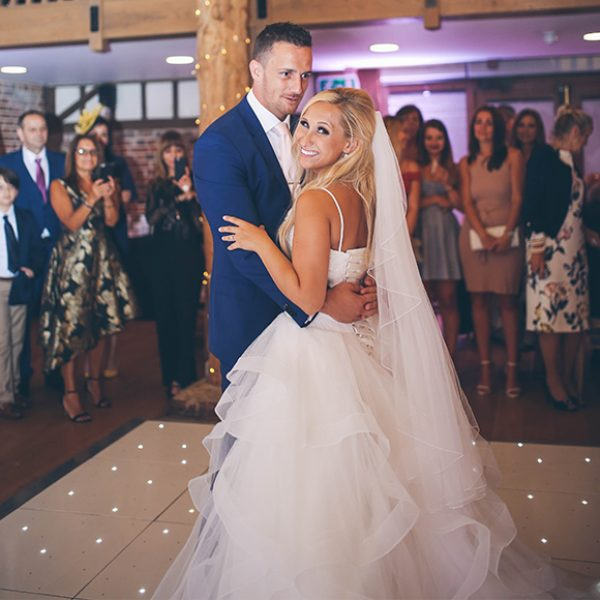 The bride and groom perform their first dance in the Mill Barn at Gaynes Park