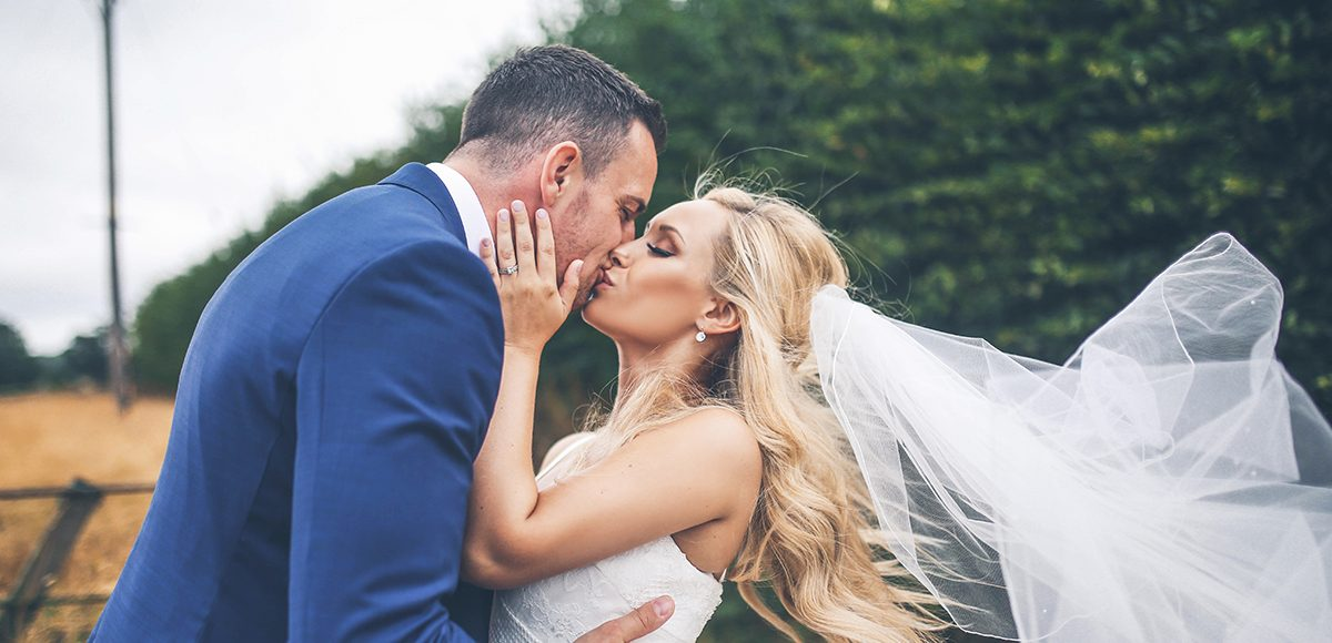 The bride and groom share a kiss on their summer wedding day at Gaynes Park in Essex
