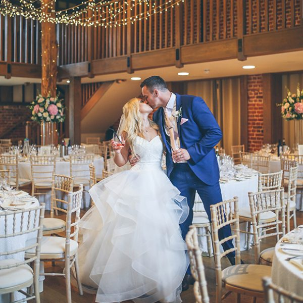 The bride and groom share a kiss in the Mill Barn at Gaynes Park before their wedding breakfast