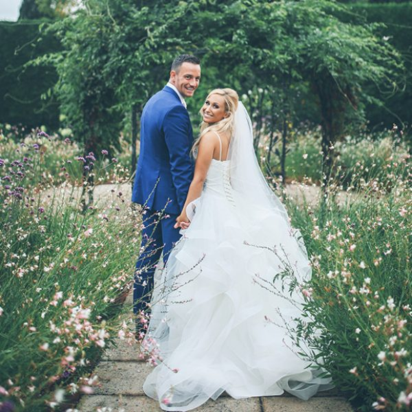 The new husband and wife take a stroll through the Walled Gardens at Gaynes Park in Essex