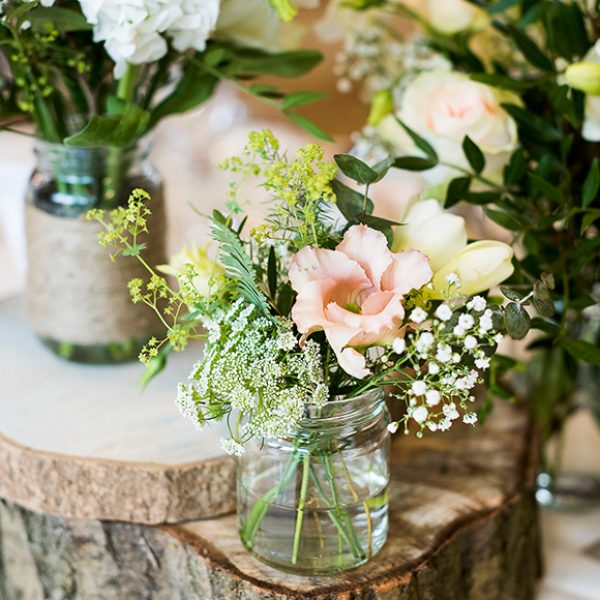 Jam jars with wedding flowers are always a hit at rustic weddings at Gaynes Park