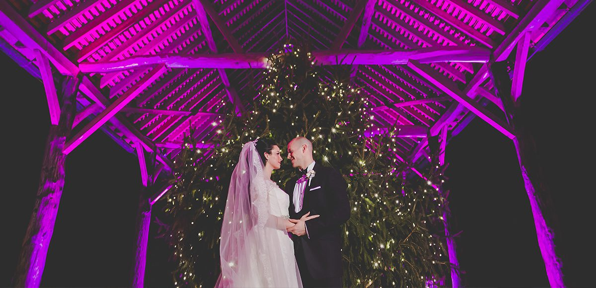 Newlyweds share a moment in front of the Christmas Tree in the Gather Barn at Gaynes Park